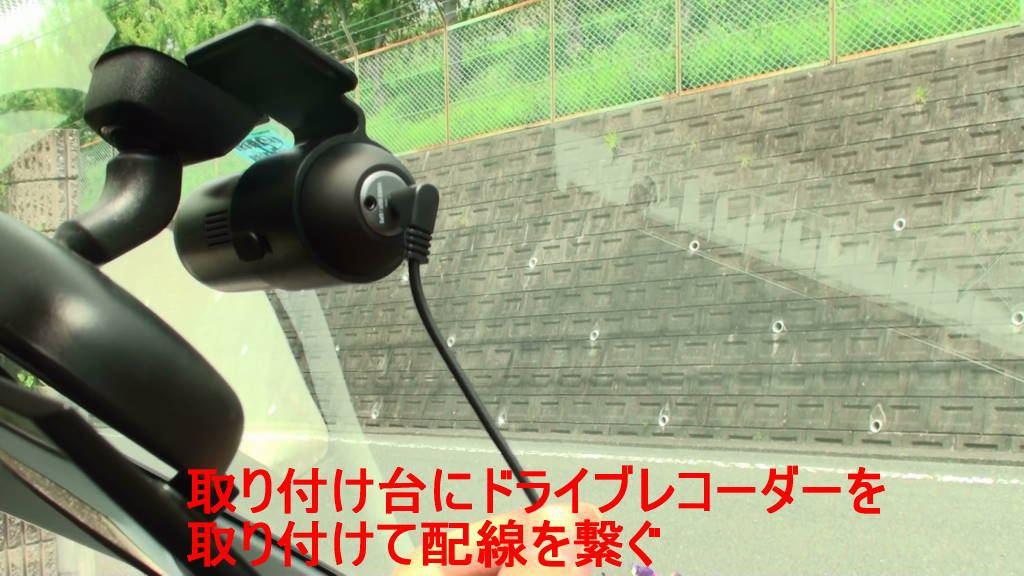 フロントガラスに貼ったドライブレコーダーの取り付け台にドライブレコーダー本体を取り付けて配線を繋ぎました。