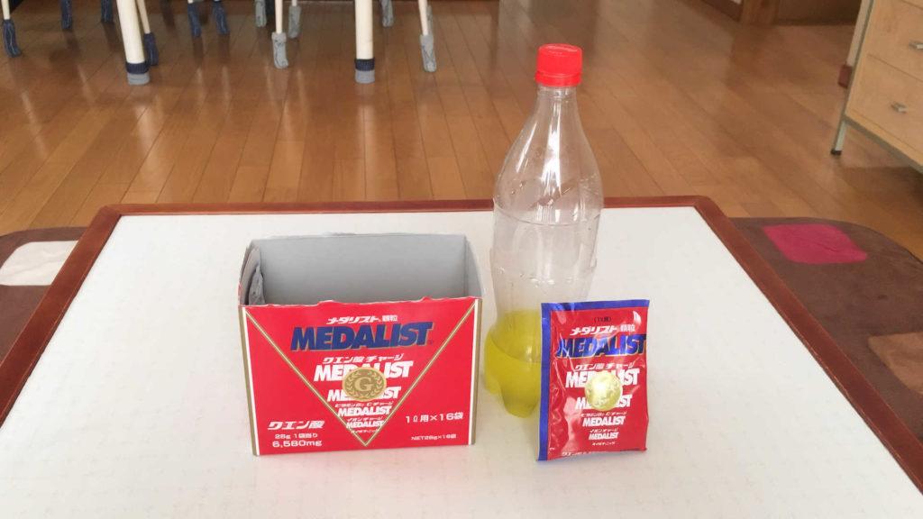 テーブルの上に置かれたアリストのメダリスト1L用の箱と中見とペットボトルに入れた状態です。